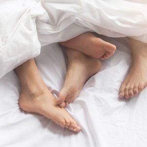pies de dos personas en la cama con sábanas blancas